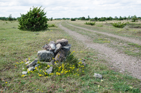 unsurfaced road: Old cairn by a dirt road side in a great plain grassland with junipers Stock Photo
