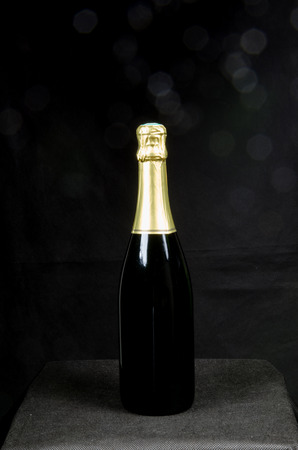 gold capped: Single bottle of sparkling wine with a black background with blurred bokeh Stock Photo