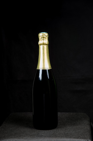 gold capped: One sealed bottle of sparkling wine at a black background Stock Photo
