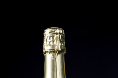 gold capped: Closeup of a sealed sparkling wine bottle cap at a black background Stock Photo