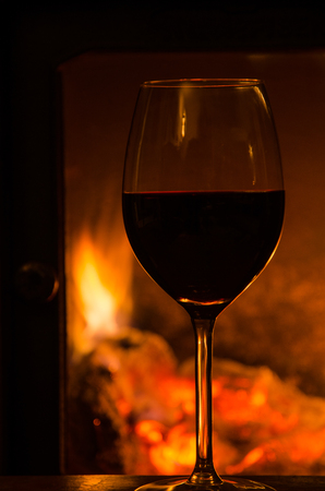 Indoors glowing fire behind a glass of red wine