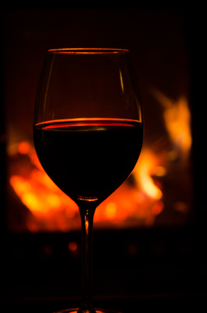 Wineglass with red wine in front of a glowing fire