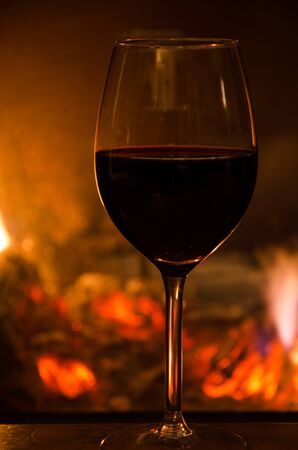 Glass of red wine on a table in front of a glowing fire
