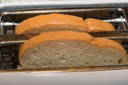 Two fresh white bread slices in a toaster