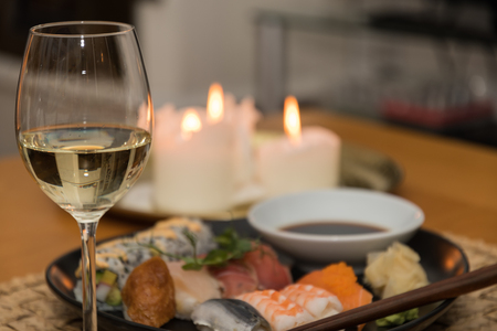 Glass of white wine in front of blurred sushi meal and candles