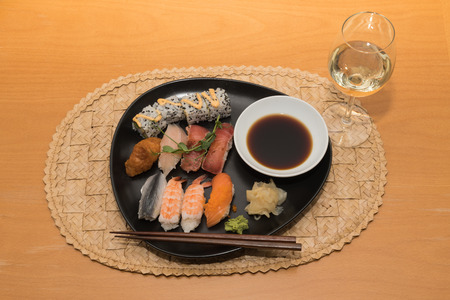 Sushi meal on a black plate with white wine on a table Stock Photo