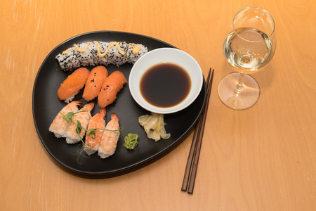The sushi meal an a glass of white wine is served