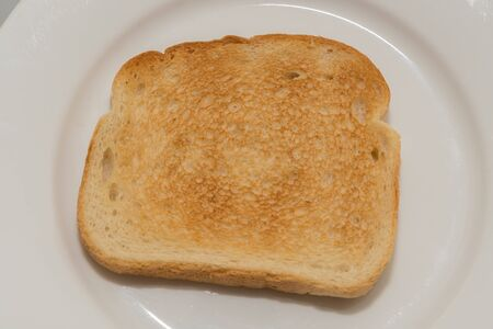 One newly toasted slice of bread on a white plate Stock Photo