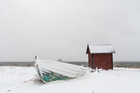 Snowy wooden rowing boat and a boathouse by the coast of the Baltic Sea in Sweden