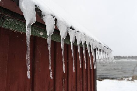 Old roof with a row of hanging icecicles