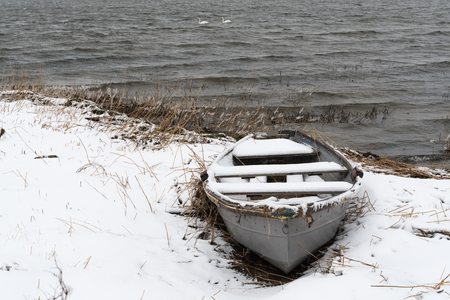Snowy old rowing boat by the coast at winter season
