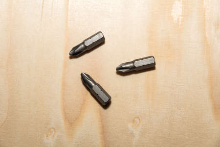 Closeup of some screw bits on a wooden surface
