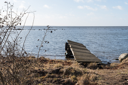 Old damaged jetty by the coast at spring season Stock Photo