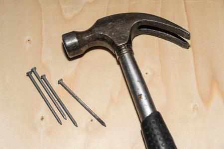 Closeup of a hammer and nails at a wooden surface
