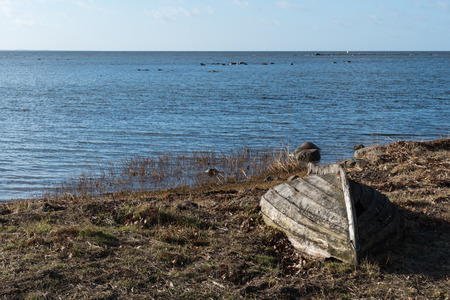 Abandoned old wooden rowing boat by the coast at spring season Stock Photo