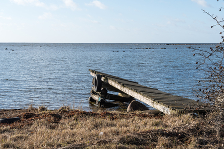 The old damaged jetty by the coast of the Baltic Sea in Sweden at spring season Stock Photo