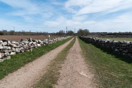 Farmers old road surrounded of old stone walls at springtime Stock Photo