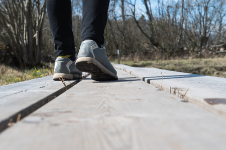 Closeup of feet walking on a wooden footpath outdoors at springtime