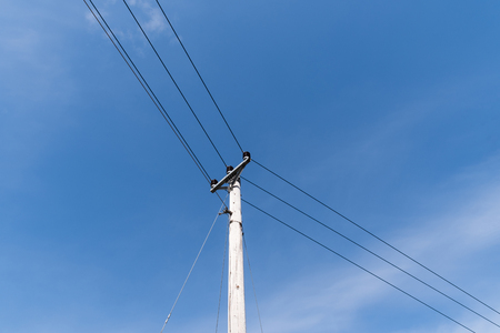 Pole with electric power lines at blue sky Stock Photo