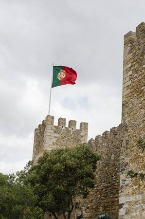 Lisbon, Portugal - April 26, 2017: Portuguese flag at the old castle Castelo Sao Jorge in Lisbon, Portugal Editorial