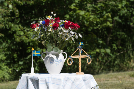 midsummer pole: Table decorated with flowers and miniatures for midsummer celebration outdoors in a garden