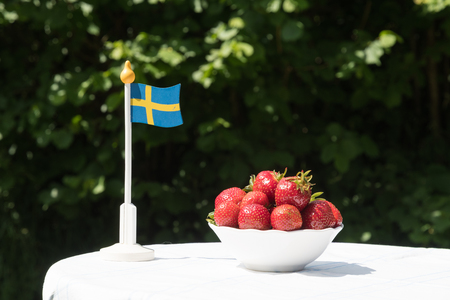 Swedish miniature flag and a bowl with fresh strawberries on a garden table