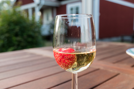 Glass with a strawberry in sparkling wine on a wooden table in a garden Stock Photo
