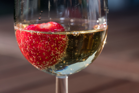 Close up of a strawberry in a glass sparkling wine