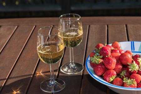 Frische Erdbeeren in einer Schüssel und zwei Gläser funkelnden Wein auf einem Holztisch Lizenzfreie Bilder