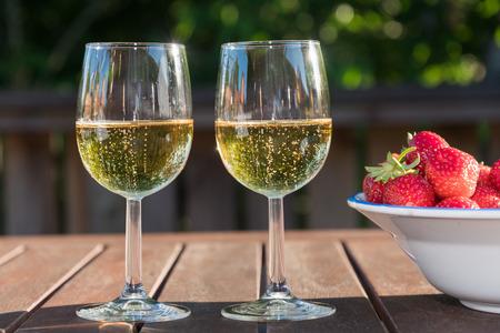 Zwei Gläser Schaumwein und Erdbeeren auf einem Holztisch am späten Abend Sonnenschein