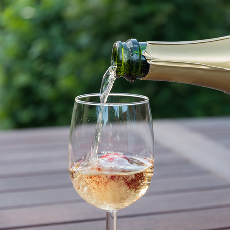 Pouring champagne from a bottle in a glass with a strawberry on a table in the garden