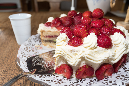 Fresh strawberry cake with a shovel and a blurred mug in the background on a table