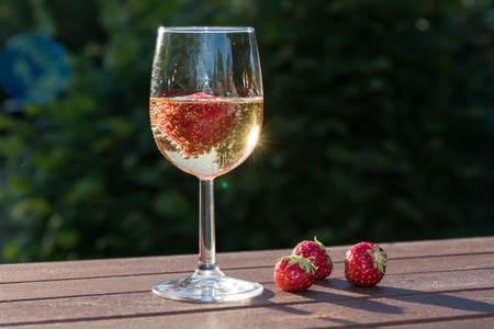 Strawberries and a glass sparkling wine on a wooden table in a garden