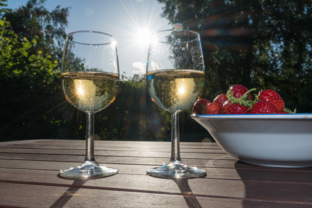 Two glasses sparkling wine and strawberries backlit on a table in late evening sunshine