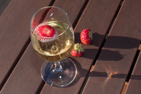 Closeup of a galss sparkling wine and strawberries on a wooden table