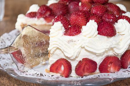 Closeup of a creamy strawberry cake with a cake shovel
