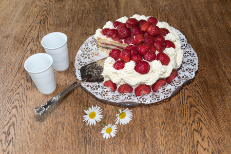 Table set for summer celebration with fresh strawberry cake, daisies and two mugs