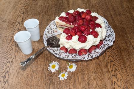 Tischset für Sommerfeier mit frischen Erdbeerkuchen, Gänseblümchen und zwei Tassen