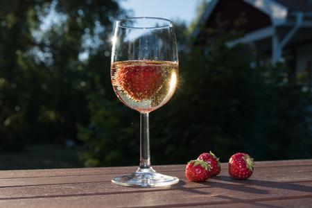 Glass with sparkling wine and strawberries on a garden table in late evening sunshine Lizenzfreie Bilder