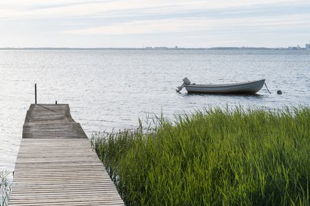 Small boat anchored in the water by an old wooden jetty at the swedish island Oland in the Baltic Sea