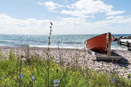 Landed red rowing boat by a colorful beach at the swedish island Oland Stock Photo