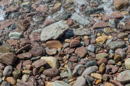 Various wet stones by the water edge Stock Photo