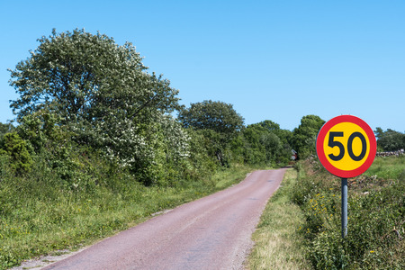 Speed limit traffic sign by a narrow road at the countryside Stock Photo