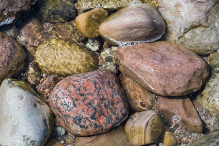 Colorful various wet stones in water
