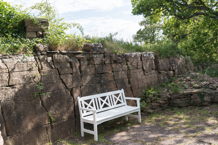 White bench by a limestone wall in a park Stock Photo