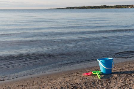 Sand beach with plastic bucket and spades