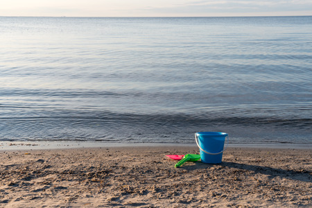 Sand beach with colorful plastic bucket and spades