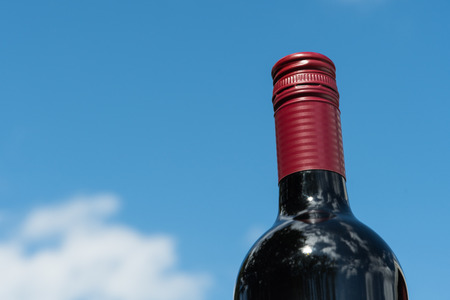 Top of a red wine bottle by a blue summer sky