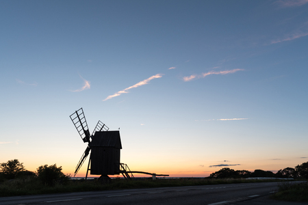 Old wooden windmill silhouette at sunset by road side at the swedish island Oland