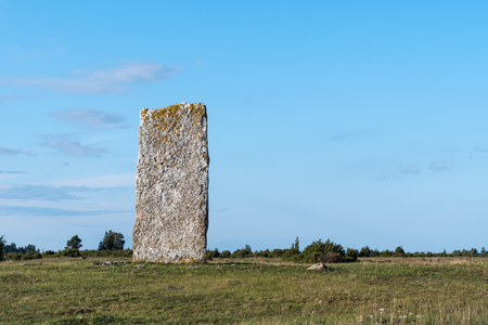 Ancient standing stone in a plain landscape at the swedish island Oland